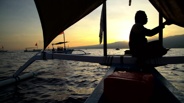 male riding outrigger canoe racing across ocean bali - bali stock videos & royalty-free footage