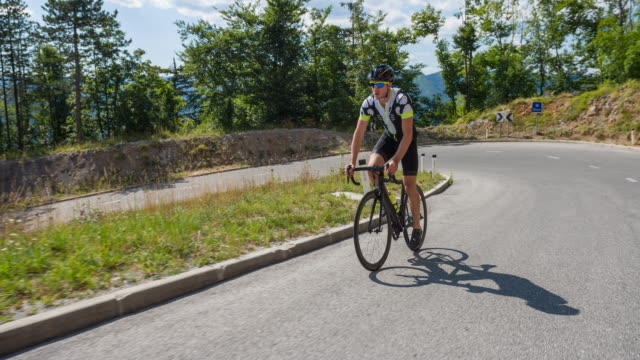 Male road cyclist cycling uphill