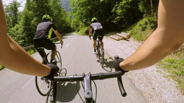 2 つの男性サイクリストの後ろに道を走行中、ハンドルを握ってpov男性の道路自転車 - dedication点の映像素材/bロール