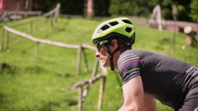 自然の中の道をペダルを押す slo mo 男性の道路自転車 - 活動点の映像素材/bロール