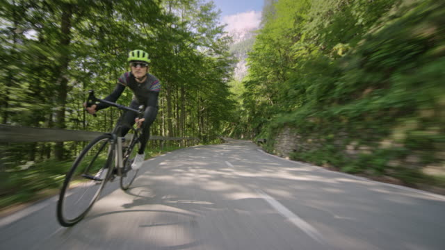 male road cyclist riding on a nice asphalt road surrounded by trees on a sunny day - slovenia stock videos & royalty-free footage