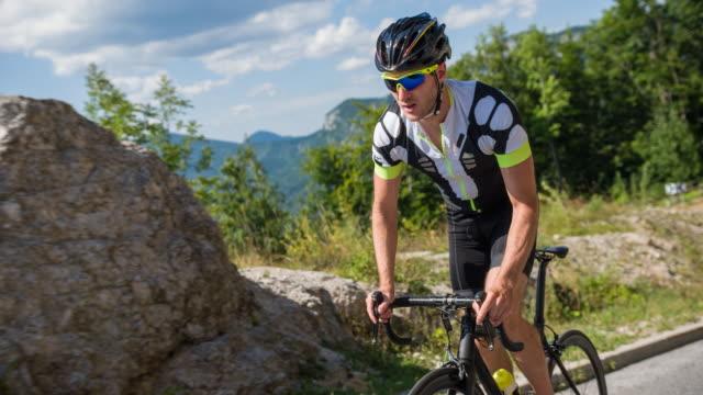 vídeos de stock, filmes e b-roll de ciclista de estrada masculino em pé enquanto o ciclismo - colina acima