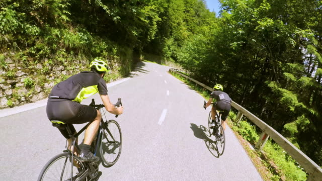 pov male road cyclists descending the mountain road on a sunny day - racing bicycle stock videos and b-roll footage