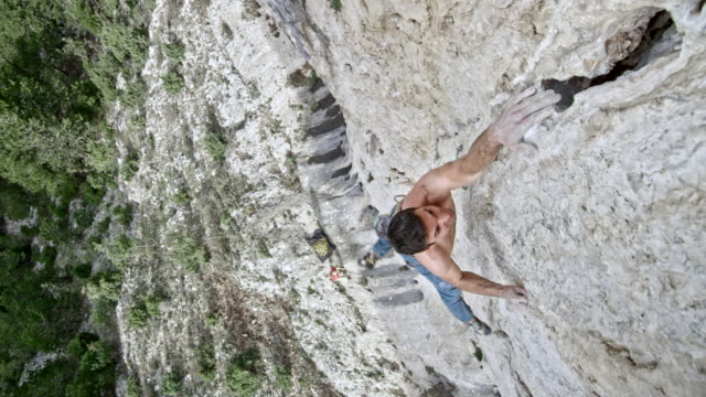male rock climber ascending a cliff, stretching out for a grip and letting go - struggle stock videos & royalty-free footage