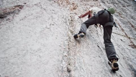 männliche kletterer aufsteigend eine weiße klippe - herausforderung stock-videos und b-roll-filmmaterial