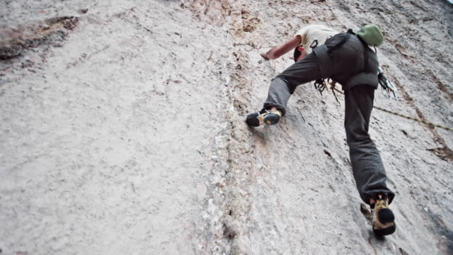 Male rock climber ascending a white cliff