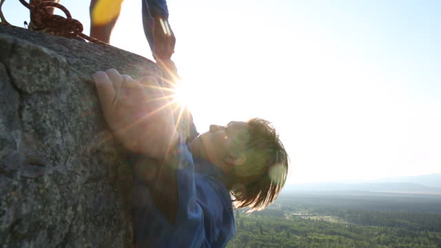male rock climber ascends vertical rock at sunrise - jacket stock videos & royalty-free footage