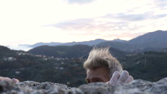 male rock climber grips rock holds at cliff edge, with chalk covered hands - gripping stock videos & royalty-free footage