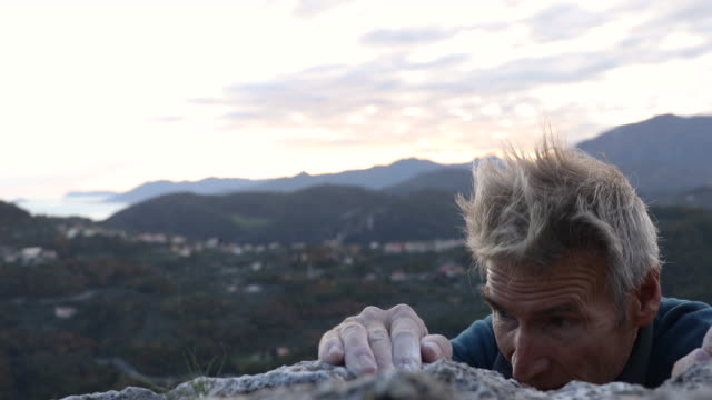 male rock climber grips rock holds at cliff edge, with chalk covered hands - top capo di vestiario video stock e b–roll