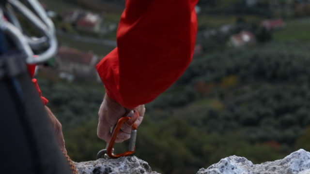 male rock climber organizes climbing gear at cliff edge, with chalk covered hands - krab stock videos & royalty-free footage