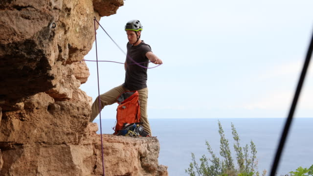 male rock climber prepares rope and gear for rappel, sea distant - eskapismus stock-videos und b-roll-filmmaterial