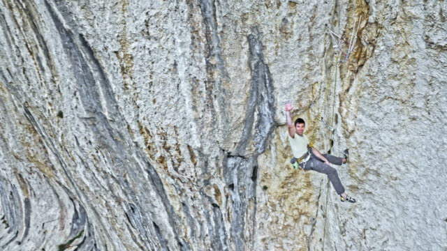 AERIAL Male rock climber waving into the camera and then descending the cliff
