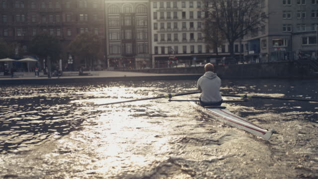 male rowing boat on river in city during sunny day - sculling stock videos & royalty-free footage