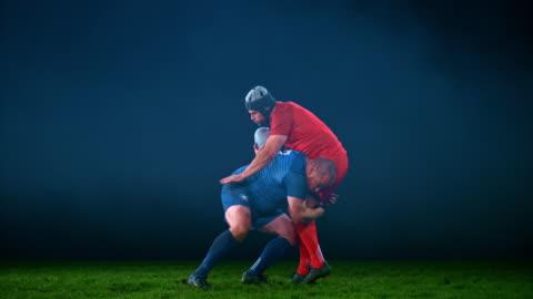 vídeos de stock e filmes b-roll de slo mo ld male rugby player tackling his opponent - râguebi desporto