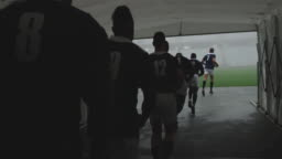 Male rugby players running together in a row at the entrance of stadium 4k