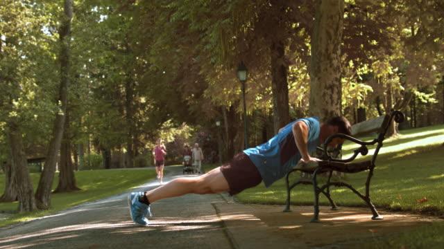 stockvideo's en b-roll-footage met ds man loper doet push ups op een bankje - oefeningen met lichaamsgewicht