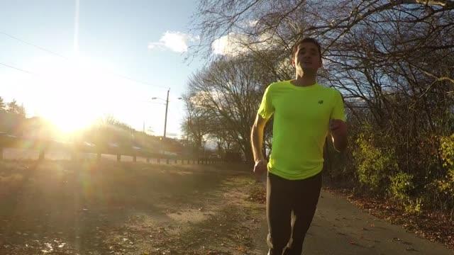 Male runner jogging at sunset through park near river