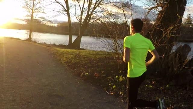 夕暮れ時の公園を通ってジョギングの男性ランナー - 20代点の映像素材/bロール