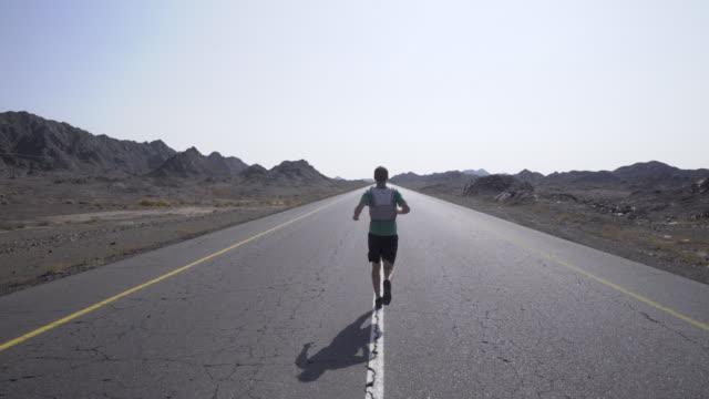vídeos y material grabado en eventos de stock de hombre corredor correr hacia abajo de la carretera pavimentada del desierto - con la espalda dando a la cámara