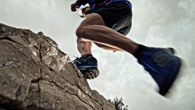 slo mo male runner jumping onto a rock on the trail in cloudy weather - inquadratura dal basso video stock e b–roll