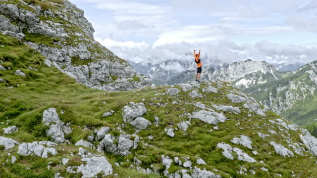 aerial male runner raising his hands in the air on the mountain top - top garment stock videos & royalty-free footage