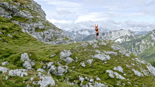 vidéos et rushes de aérienne coureur masculin, levant ses mains en l'air sur le sommet de la montagne - chaîne de montagnes