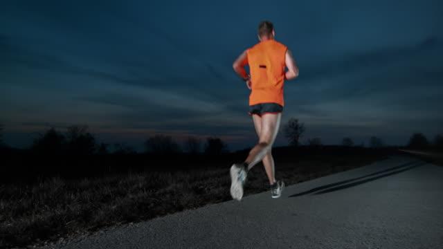 SLO MO DS Male runner running at night