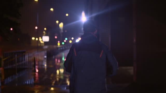 SLO MO-TS männliche Läufer laufen in der Stadt bei Nacht