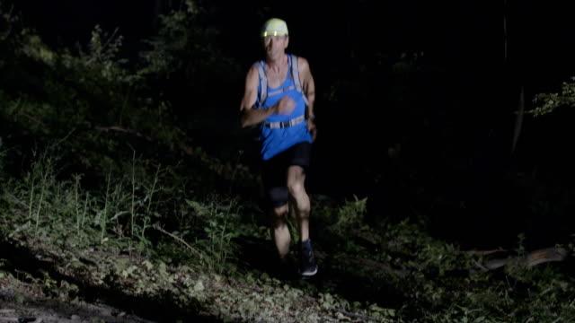 SLO MO manliga löpare springer i skogen på natten