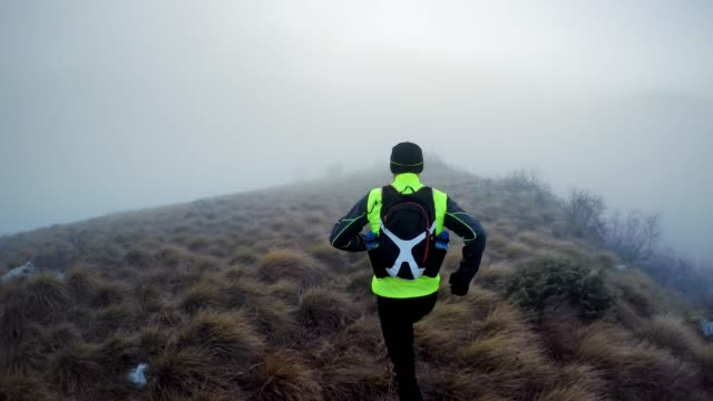 male runner running on a grassy mountain trail on a cold morning in fog - one man only stock videos & royalty-free footage