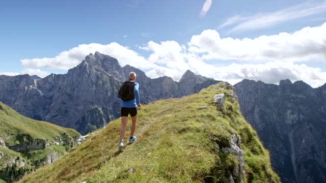slo mo male runner running on the edge of a mountain ridge in sunshine - top garment stock videos & royalty-free footage