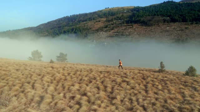 aerial male runner running on the foggy mountain - jacket stock videos & royalty-free footage