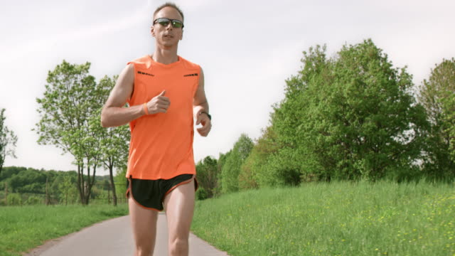 SLO MO TS Male runner running through countryside in sunshine