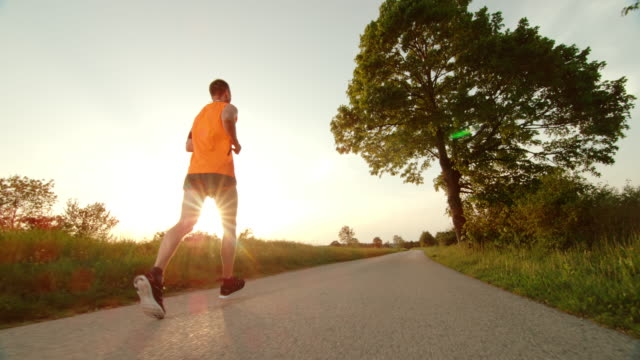 SLO MO TS Male runner running through the countryside at sunset