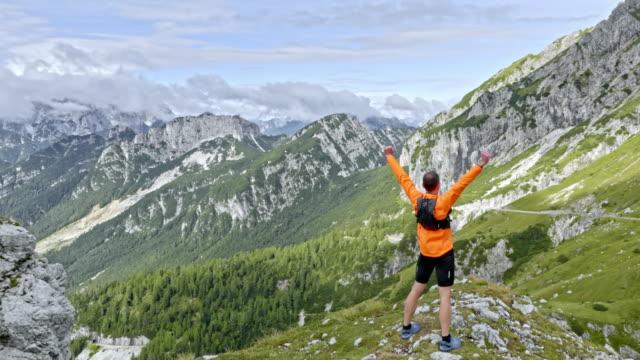 vídeos y material grabado en eventos de stock de corredor macho aéreo hasta la cima de la montaña en sol y levantar las manos en la victoria - top