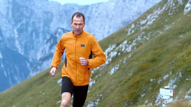 SLO MO mannelijke loper loopt een parcours hoog in de bergen