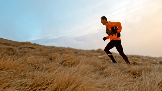 slo mo male runner running up the grassy slope - orange colour stock videos & royalty-free footage