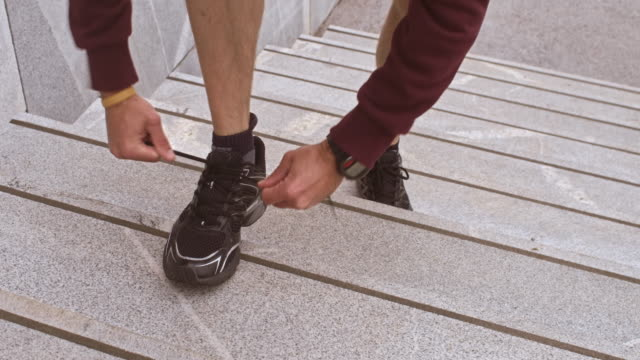 LD Male runner stopping on stairs to tie a shoelace