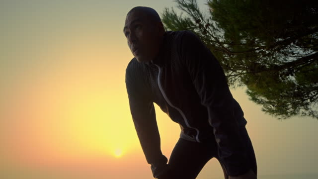 slo mo male runner stopping on the pathway leading by the sea to catch a breath in the morning sun - cardiovascular exercise stock videos & royalty-free footage