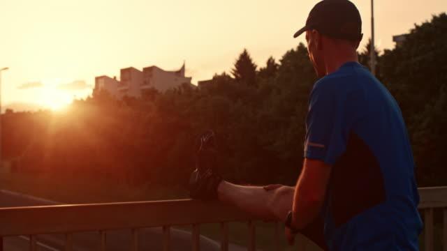 vídeos y material grabado en eventos de stock de mo masculino corredor de san luis obispo de estiramiento su pierna al atardecer - 35 39 años