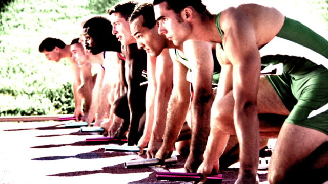 OVEREXPOSED SELECTIVE FOCUS male runners holding batons on track raise heads in unision / start race