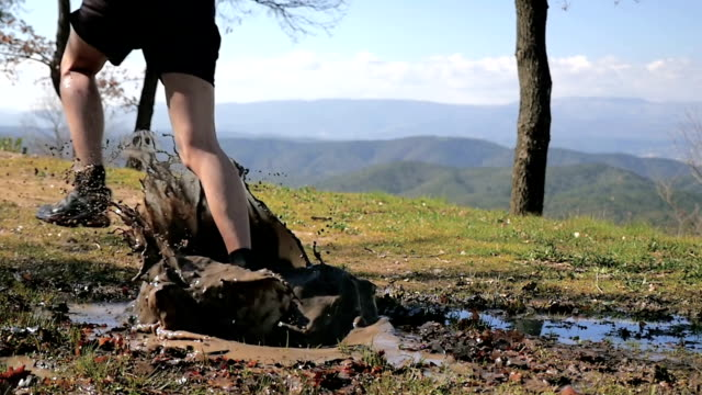male running outdoors and jumping in a puddle - mud stock videos & royalty-free footage