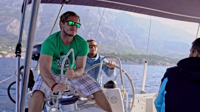 4k männlichen segelteam anpassung der takelage auf segelboot auf sonnigen meer, real-time - segelmannschaft stock-videos und b-roll-filmmaterial