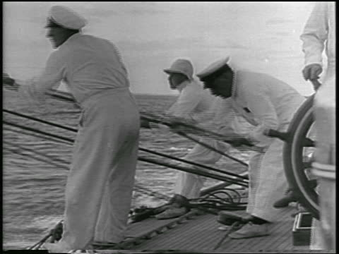 B/W 1934 male sailors in white pulling ropes on sailboat in America's Cup race