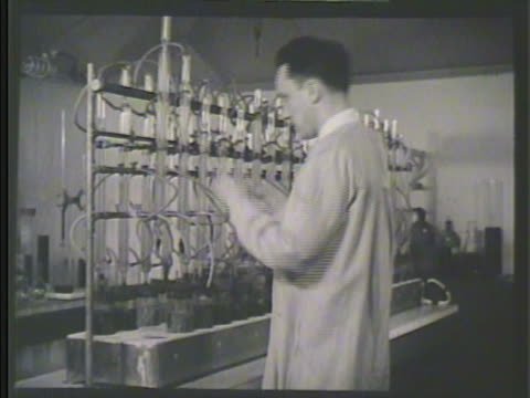 male scientist adding jar w/ metal strip motor cooling solution to air tubes in lab for testing mcu inserting air tubes into top of jar creating... - liquid solution stock videos and b-roll footage