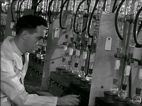B/W 1948 male scientist adjusting knobs on test tubes with bubbling liquid