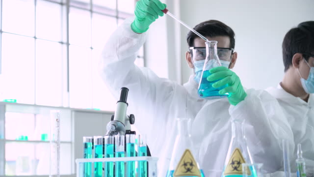 male scientist carefully measuring chemicals in a laboratory - folding stock videos & royalty-free footage