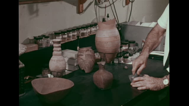 Male scientist in laboratory dating ancient Egyptian clay jar grinding fragment into powder placing aluminum disc into machine printer graphing...
