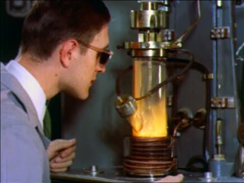 vídeos y material grabado en eventos de stock de 1957 male scientist in safety glasses looking at glowing experiment / bell labs - 1957