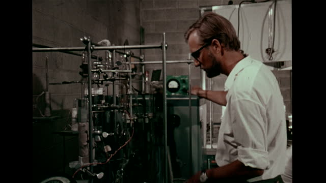 Male scientist in University of Pennsylvania laboratory examining meter on scientific equipment MS Geophysicist Henry Faul adjusting dials on...